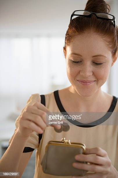 Woman putting coins in purse
