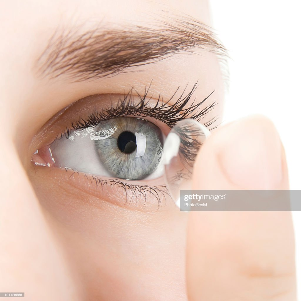 Woman putting contact lens into eye : Stock Photo