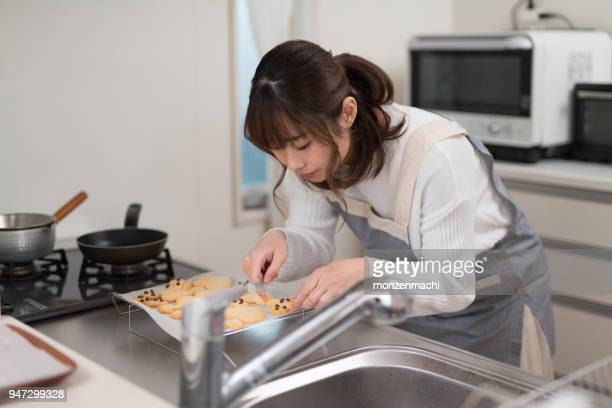 Woman putting cookie on paper