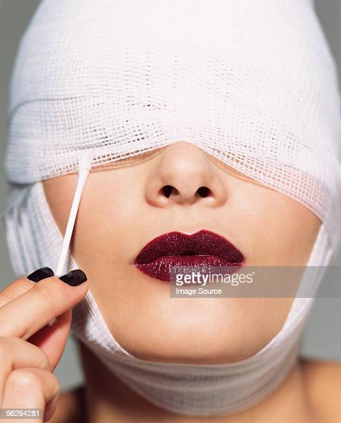 Woman putting cotton bud under bandage