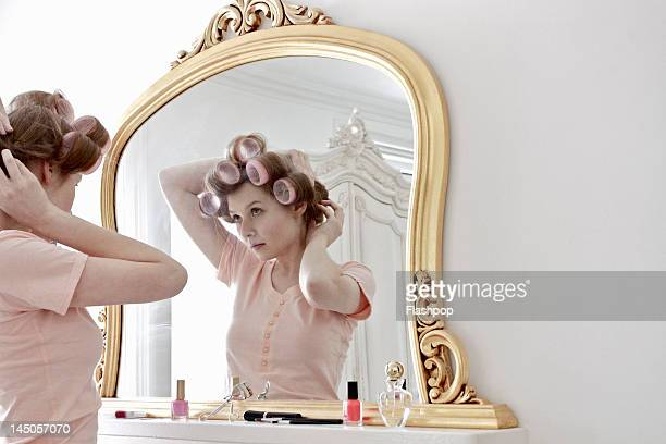 Woman putting curlers in her hair