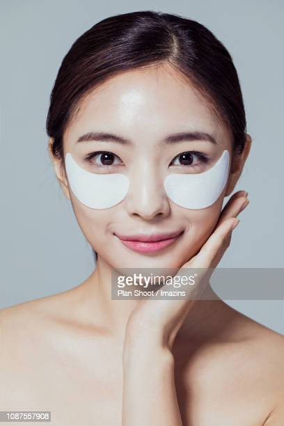 woman putting eye patch - korean ethnicity stock pictures, royalty-free photos & images