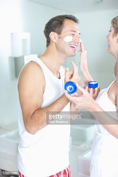 Femme mettant crème pour le visage sur mari ''s visage