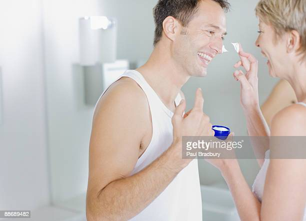 Woman putting face cream on husbands face