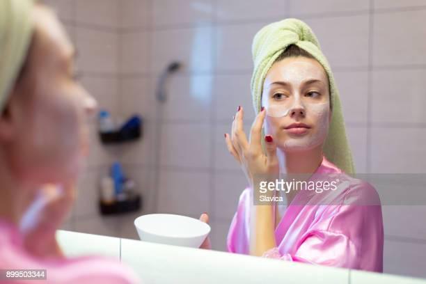 frau weglegen gesichtsmaske im badezimmer - faltenreduktion stock-fotos und bilder