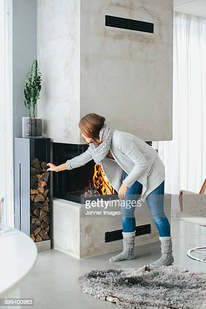 Woman putting firewood in fireplace