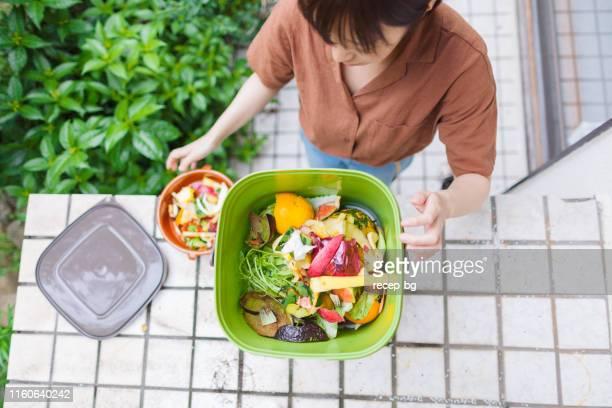 femme mettant des ordures de nourriture dans le composteur - humus photos et images de collection
