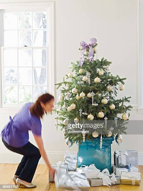 Woman putting gift under Christmas tree