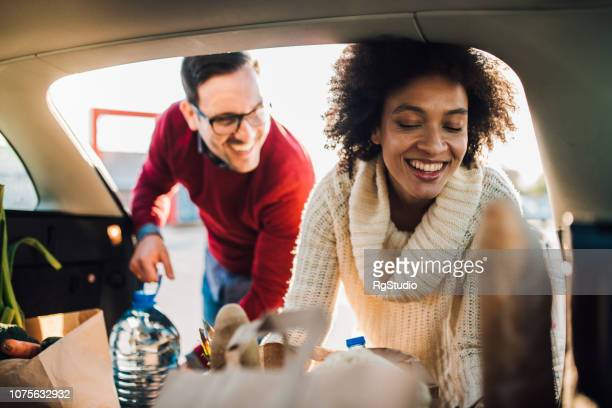 woman putting groceries in a car - car trunk stock pictures, royalty-free photos & images