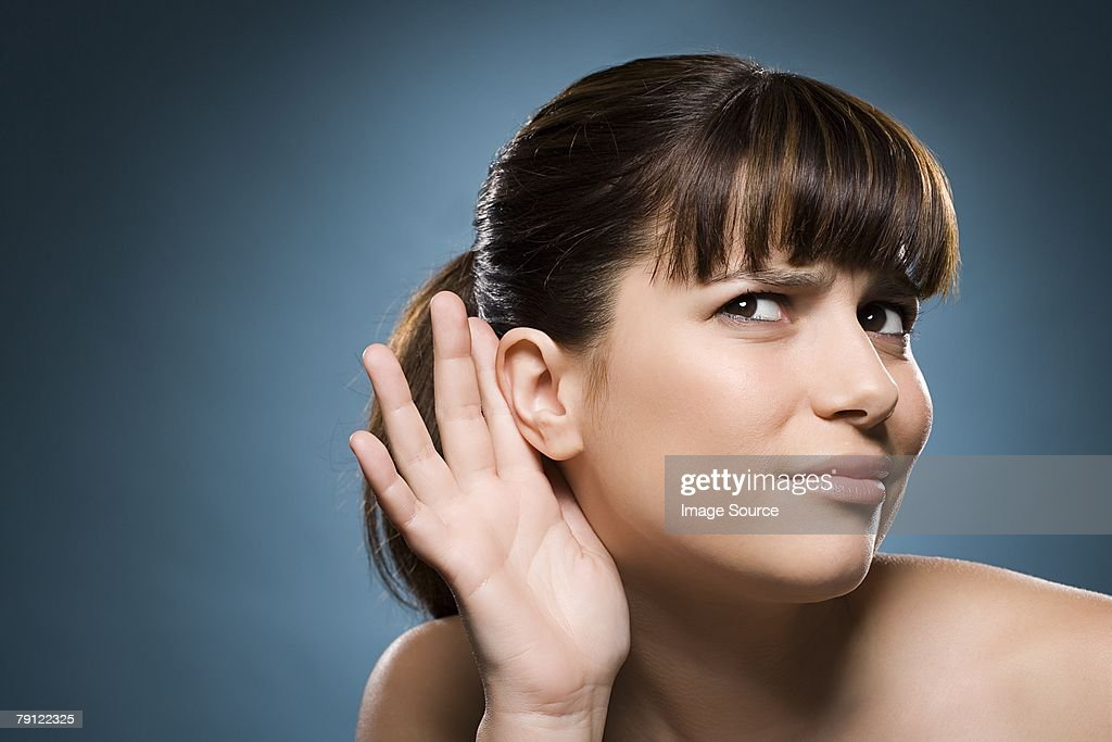 Woman putting hand to her ear : Stock Photo
