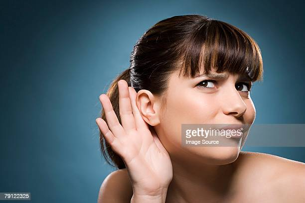 woman putting hand to her ear - luisteren stockfoto's en -beelden