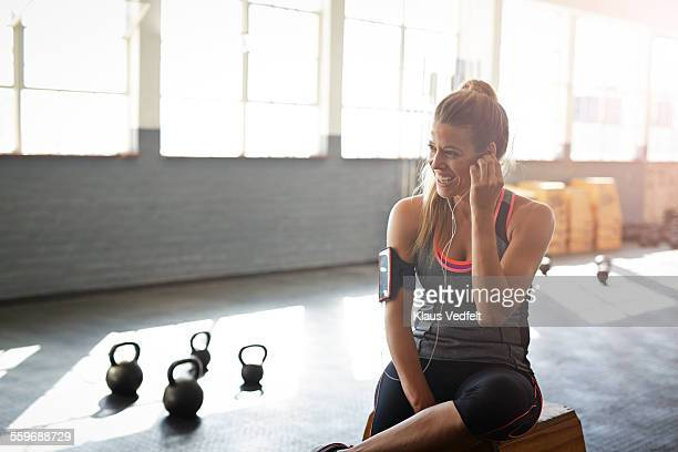 Woman putting headphones in ear at gym gym