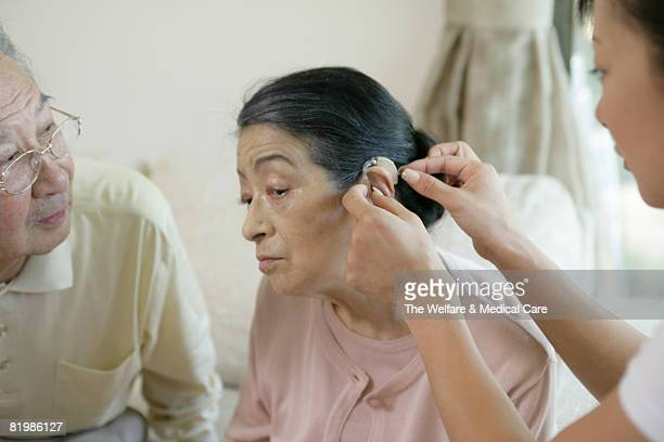 Woman putting hearing aid on mature woman