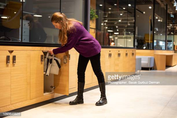 Woman putting her bag into a safety deposit box