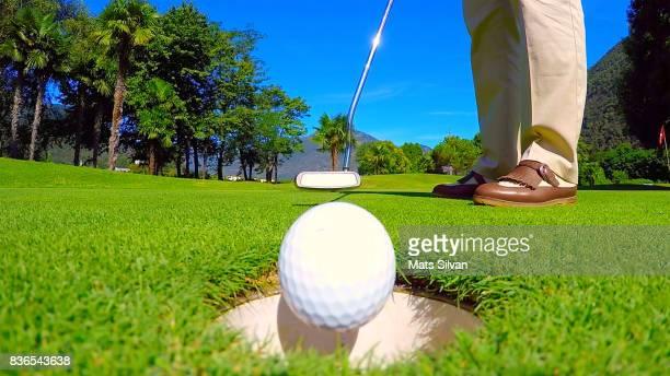 woman putting her golf ball in the hole - einlochen golf stock-fotos und bilder