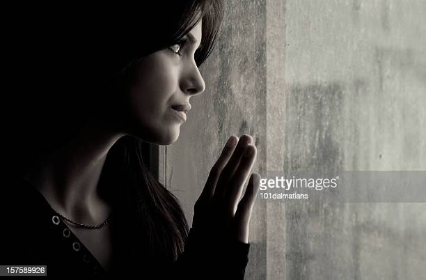 A woman putting her hand on a window and looking out