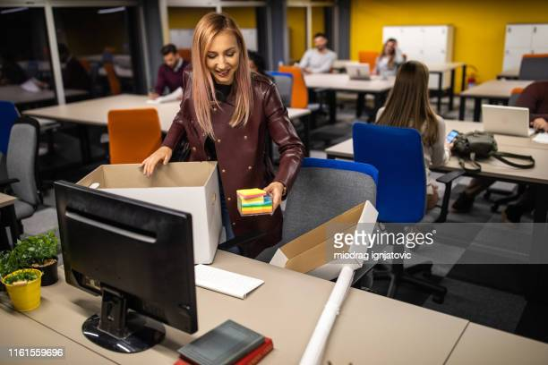 woman putting her plant on table in  new office - day 1 stock pictures, royalty-free photos & images