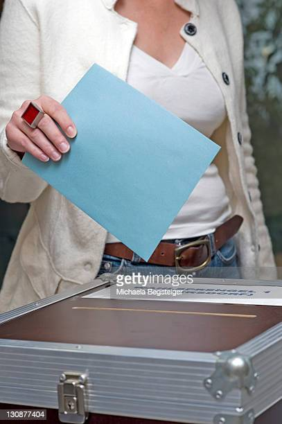 Woman putting her vote into the voting box