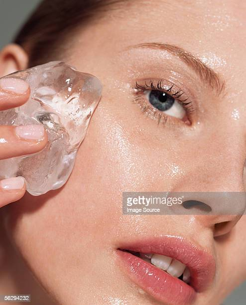 Woman putting ice on her face
