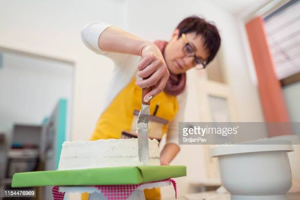 woman putting icing with spatula - cake decoration stock pictures, royalty-free photos & images