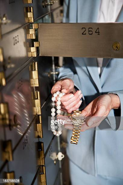 woman putting jewelry in safety deposit box - safety deposit box stock pictures, royalty-free photos & images