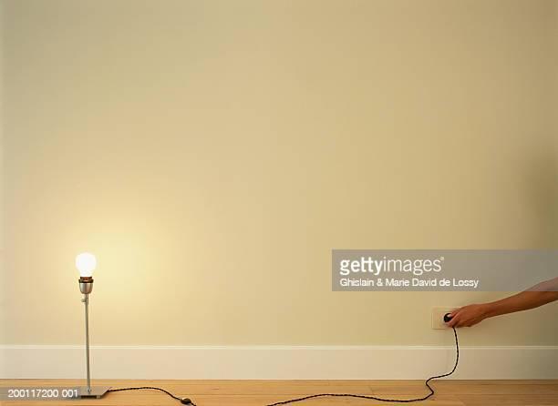 Woman putting lamp plug into socket