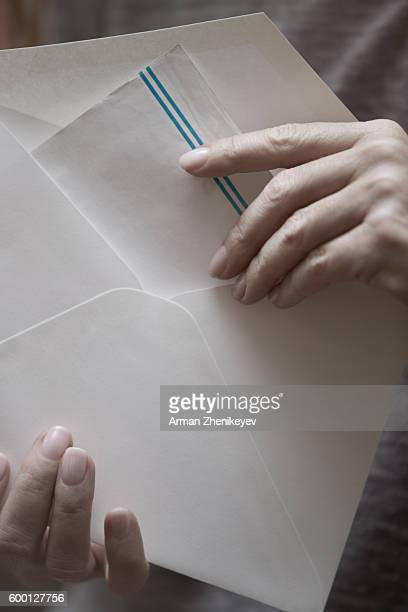 Woman putting letter to envelop