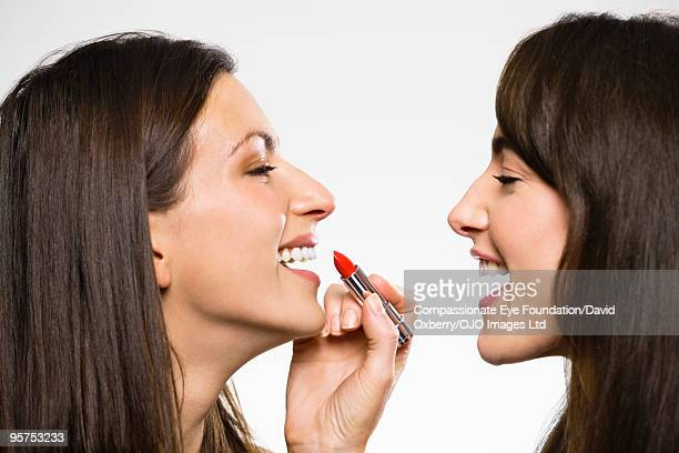 woman putting lipstick on another woman - cef do not delete stock pictures, royalty-free photos & images