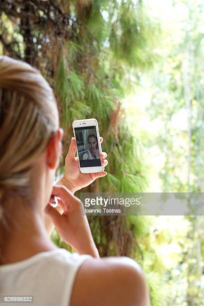 Woman putting lipstick using her phone camera