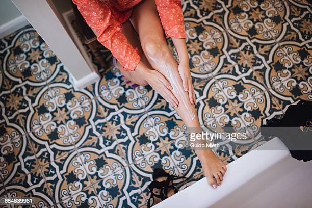 woman putting lotion on her leg. - low section stock pictures, royalty-free photos & images