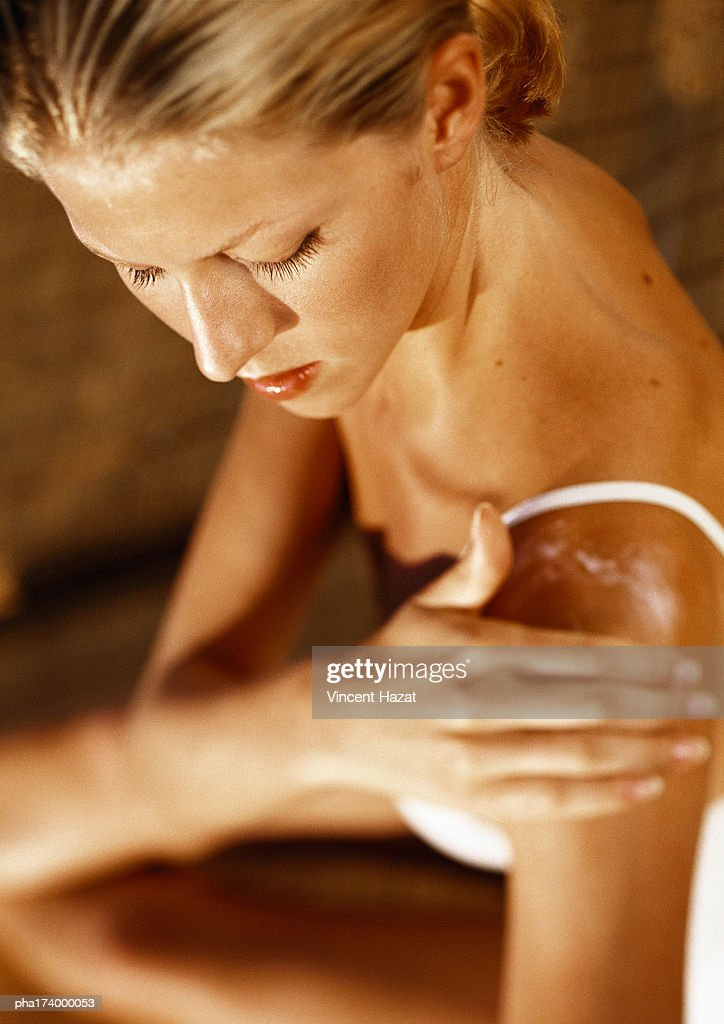 Woman putting lotion on shoulder : Stockfoto