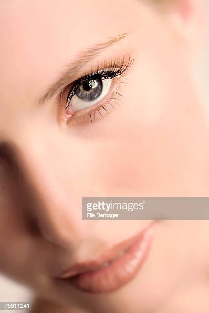 Woman putting make-up base on her cheek, close-up, indoors (studio)