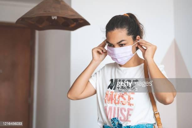 mulher colocando máscara em seu rosto antes de sair de casa - ir embora - fotografias e filmes do acervo