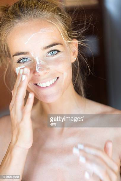 woman putting moisturizer on her face, perfect candid smile - sunscreen stock photos and pictures
