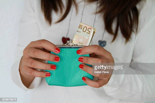 Woman putting money in change purse, close-up