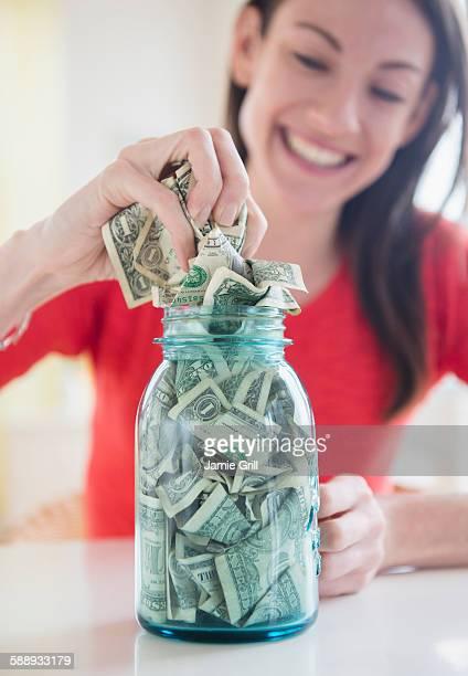 Woman putting money into jar