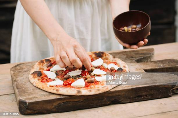 Woman putting olives on homemade pizza, mid section