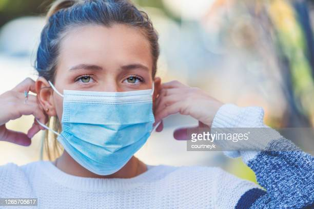 woman putting on a protective surgical face mask outdoors. - avoidance stock pictures, royalty-free photos & images