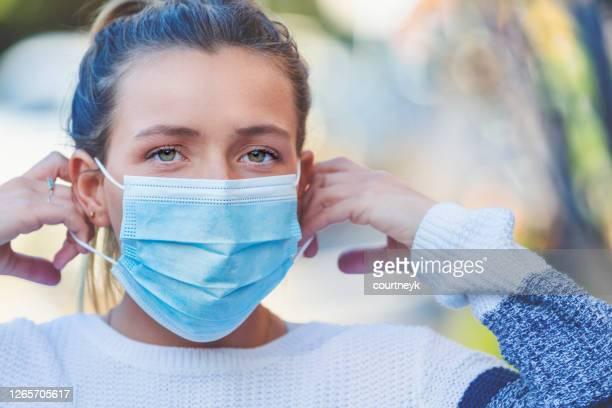 mujer poniéndose una mascarilla quirúrgica protectora al aire libre. - evitar fotografías e imágenes de stock