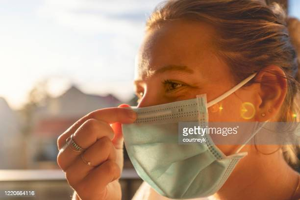 woman putting on a surgical face mask. - nose mask stock pictures, royalty-free photos & images