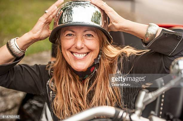 Woman Putting on a Vintage-style Biker's Helmet