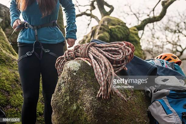 Woman putting on climbing harness