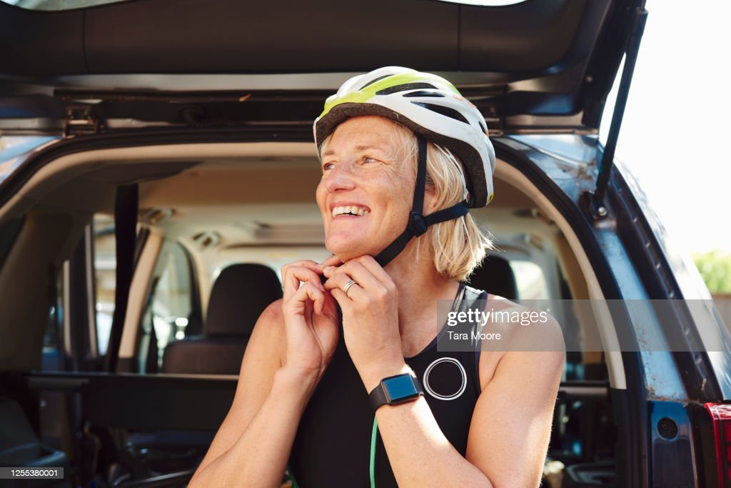woman putting on cycling helmet : Stock Photo