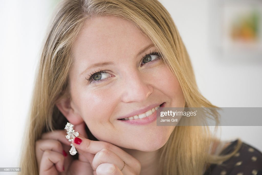 Woman putting on earring, smiling : Stock Photo