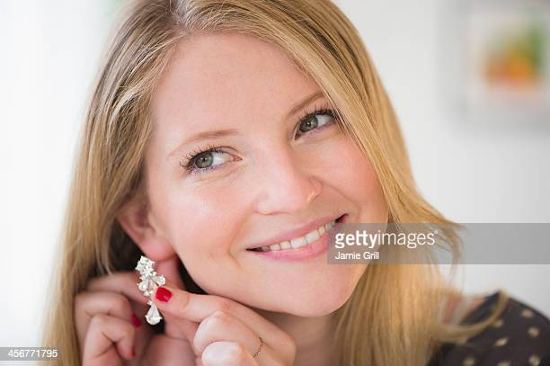 woman putting on earring, smiling - ohrring stock-fotos und bilder