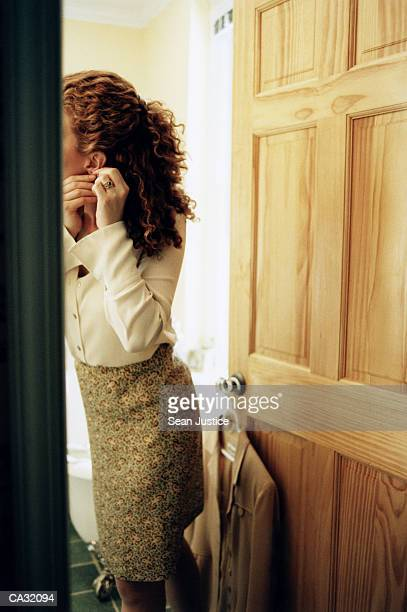 woman putting on earrings in bathroom - getting dressed stock pictures, royalty-free photos & images