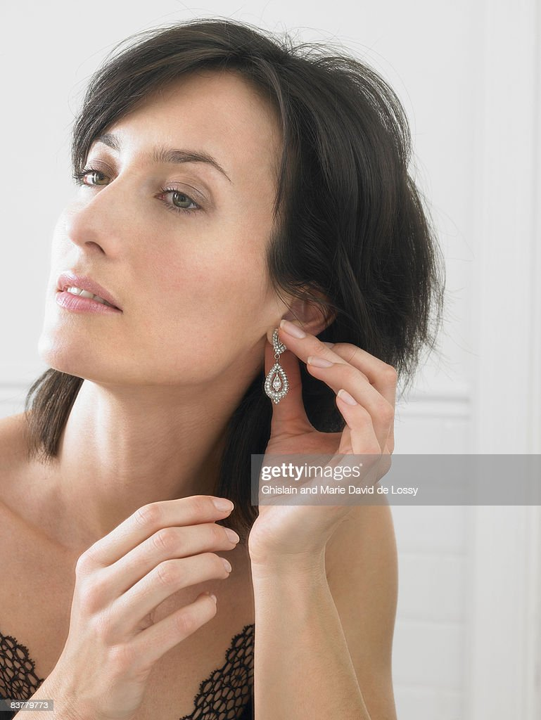 photo putting earrings stock alamy woman in