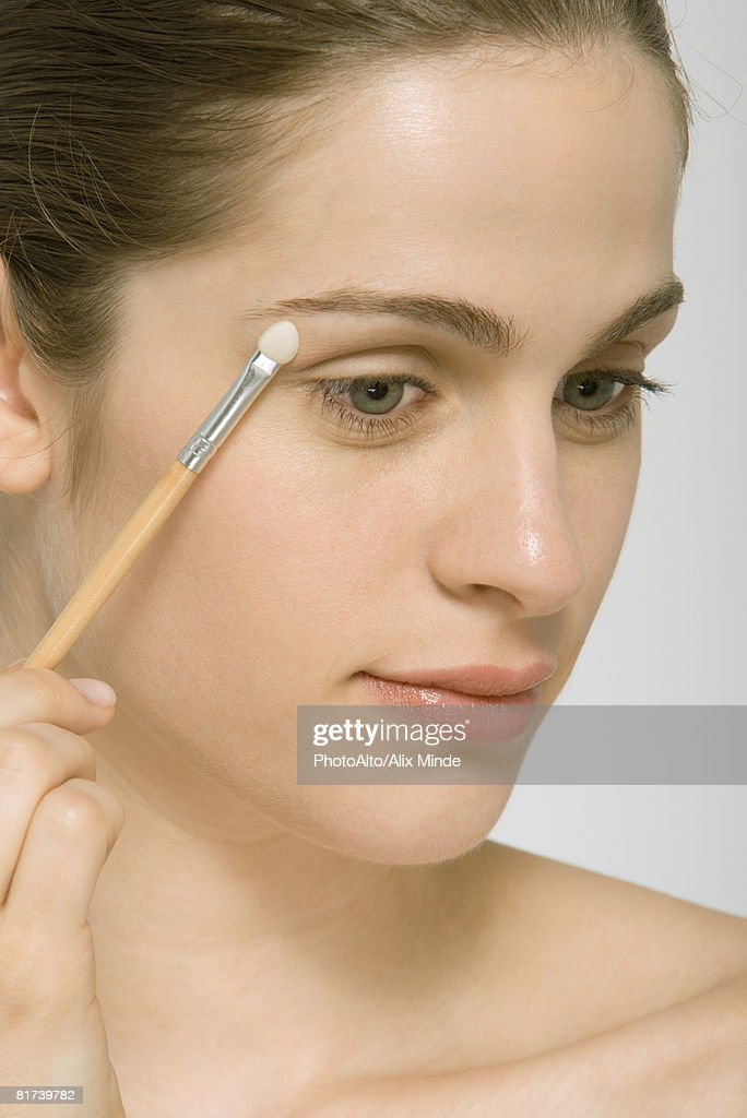 Woman putting on eye shadow, close-up : Stock Photo