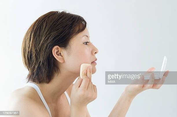 woman putting on foundation - powder compact stock pictures, royalty-free photos & images