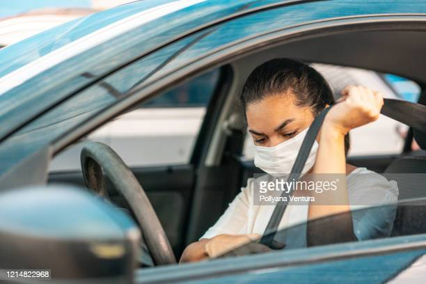 woman putting on her car seat belt - driving mask stock pictures, royalty-free photos & images
